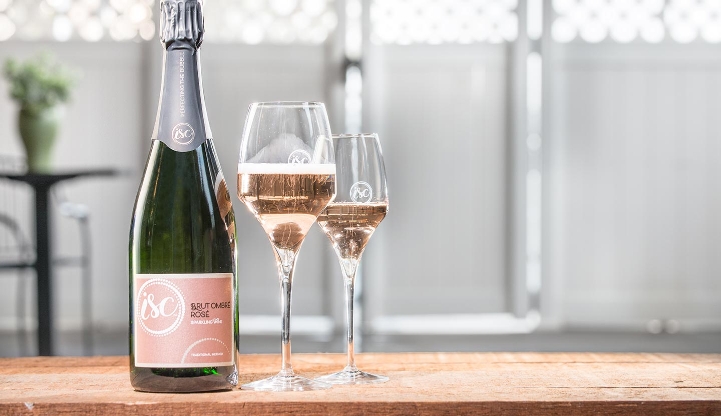 Bottle and two glasses of ISC Brut Ombré Rosé sparkling wine